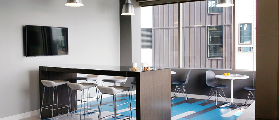 Break room area with high top seating, tv and small tables