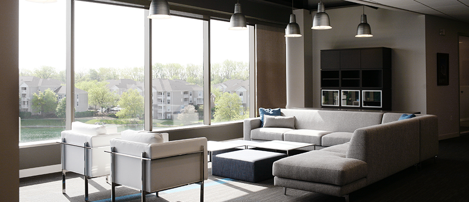 Waiting room area with grey couch and white chairs