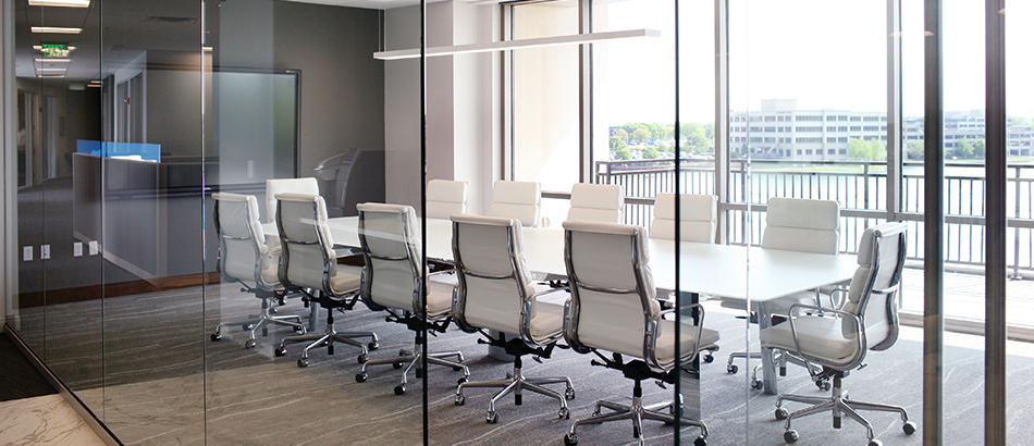 Conference room with white chairs and tables, all glass walls