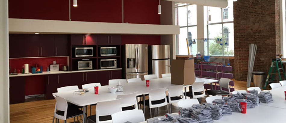 Kitchenette area with red walls, white tables and bricks