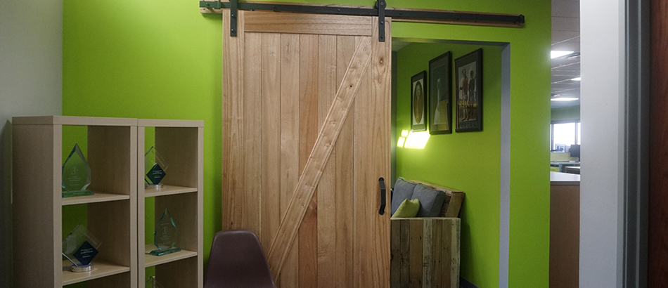 Green wall with sliding light wood barn door