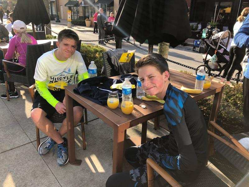 Two kids sitting at outdoor table with orange juice after a race