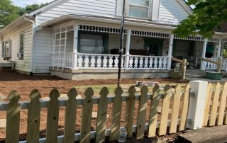 Exterior of small home with picket fence