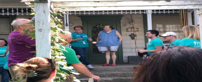Woman standing on porch with people looking at them in yard
